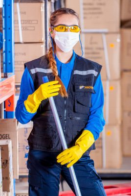 A woman holding a mop or broom wearing safety gear and a medical face mask. Manufacturers should focus on grooming their workforce in 2021.