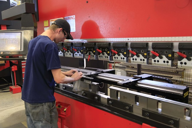 A metal worker working on a hydraulic press. If you cross-train your employees, you can avoid a worker shortage
